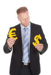 Businessman Choosing Between Euro And Dollar Signs