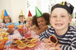Young children eating jam tarts at birthday party