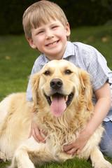 Young boy in garden with golden retriever
