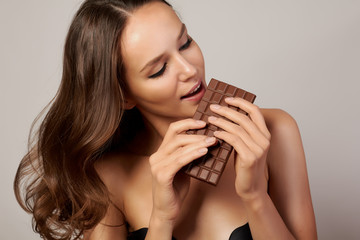 Beautiful girl with chocolate to enjoy the taste and are dieting