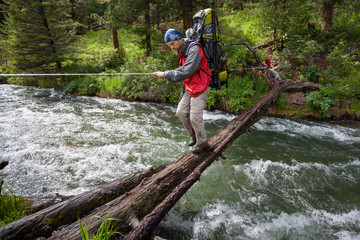 Backpackers are crossing mountain river by wooden log in Altai m