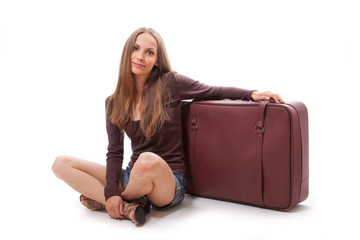 Girl sitting near a suitcase, isolated on white