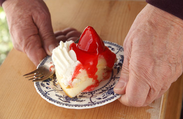 Man with strawberry-topped cake