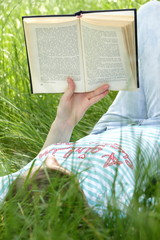 Girl is reading the book laying on grass