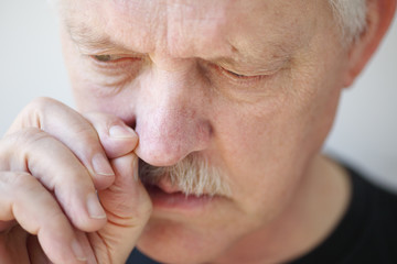 Man with stuffy nose pulls on a nostril