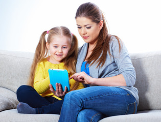 Mother with daughter sitting on sofa home work learning.