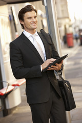 Businessman standing at bus stop using tablet
