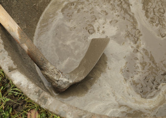 spade and wet cement for construction process