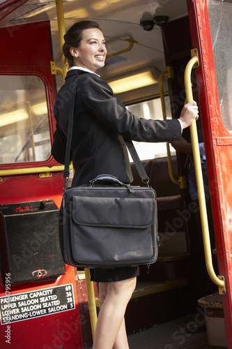 Businesswoman standing on Routemaster bus platform Poster