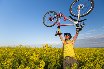 Mtb biker is holding bicycle above his head in yellow rapeseed f