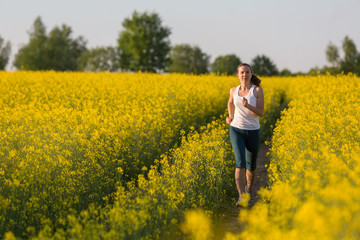 Young woman is jogging in yellow rapeseed field at sunset