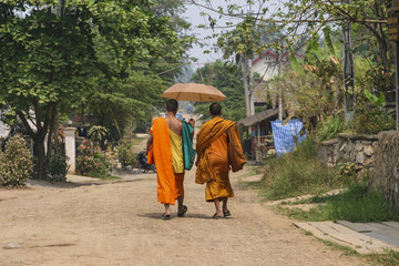 Monks with umbrella in Luang Prabang, Laos..