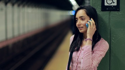 Young Latina hispanic woman in city talking on cellphone