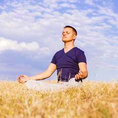 The peaceful scenery of a man meditating in the lotus position.