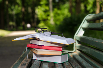 Books, glasses and open book on top of the green bench