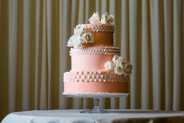 Pink and white wedding cake on white table