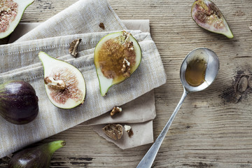 Figs, honey and nuts on wooden table