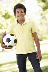 Boy in park holding football