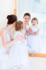 Beautiful mother and daughter at a mirror