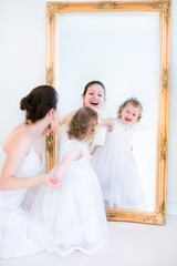 Pretty mother and daughter at a mirror