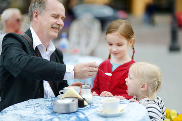 Grandfather feeding frothy milk to his grandchild