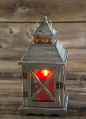 Asian Lantern and burning large red candle inside on weathered w