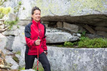 Sportliche Frau beim Nordic Walking zwischen Felsen