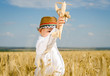 Little boy flying a toy plane in a wheat field