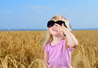Cute little blond girl playing in a wheat field