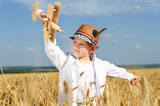 Trendy young boy playing in a field with a plane