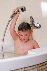 Cute small boy showering in the bath
