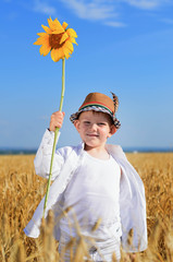 Boy holding a sunflower in the middle of a field
