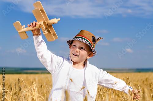 Little boy flying a toy plane in a wheat field