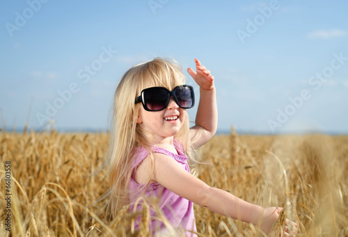 Adorable little blond girl in huge sunglasses