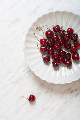 Cherries on a plate on a marble table