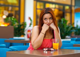 attractive sad girl drinking juice in bar
