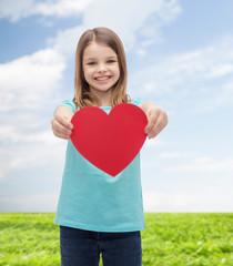 smiling little girl giving red heart