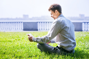 Man with laptop sitting on green lawn in park