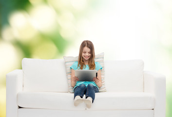 little girl sitting on sofa with tablet pc