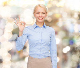 smiling businesswoman showing ok-sign with hand