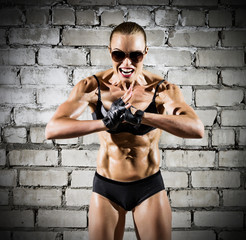 Muscular woman on brick wall (dark version)