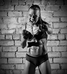 Muscular woman on brick wall (monochrome version)