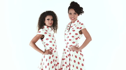 Two multi cultural models posing on white background