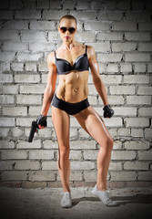 Muscular woman with gun on brick wall (normal version)