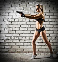 Muscular woman with gun on brick wall (dark version)