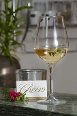 Weinglas auf Bartresen mit Karte Cheers