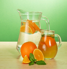 Jug with drink, jug tea and oranges