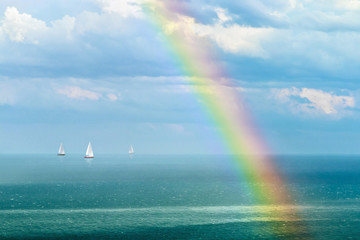 landscape with a rainbow after the rain and sailboats