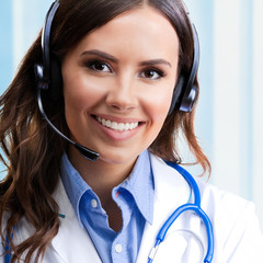 Smiling young doctor in headset, at office