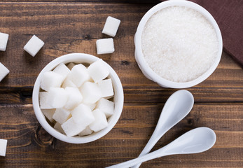 White sugar in bowls  on wooden background.
